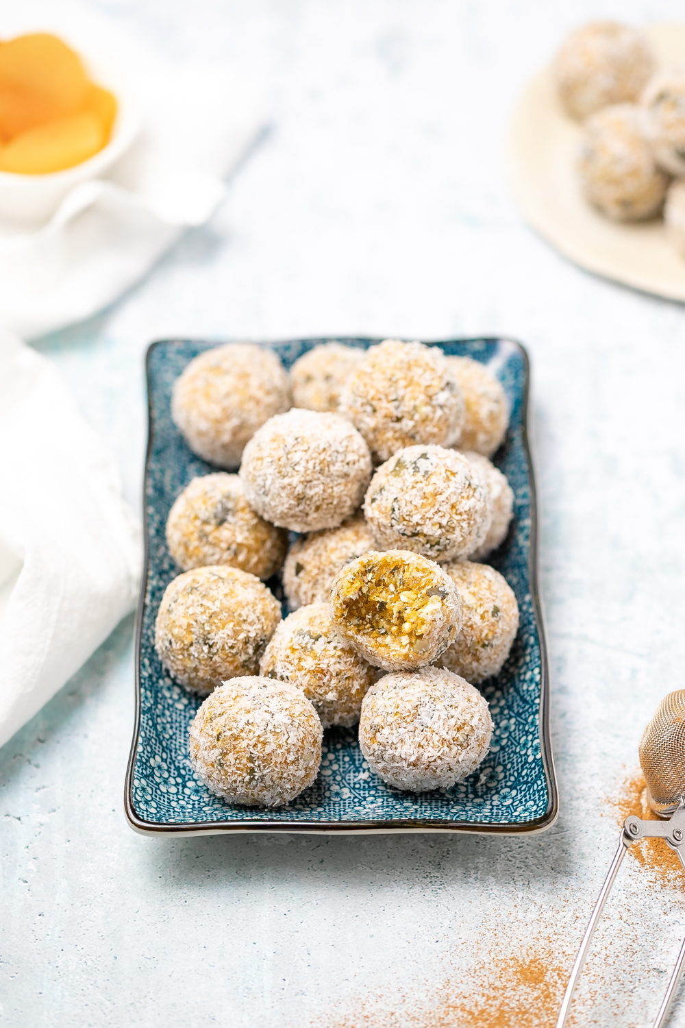 small blue rectangular plate of apricot bliss balls rolled in desiccated coconut, dish of honey in background