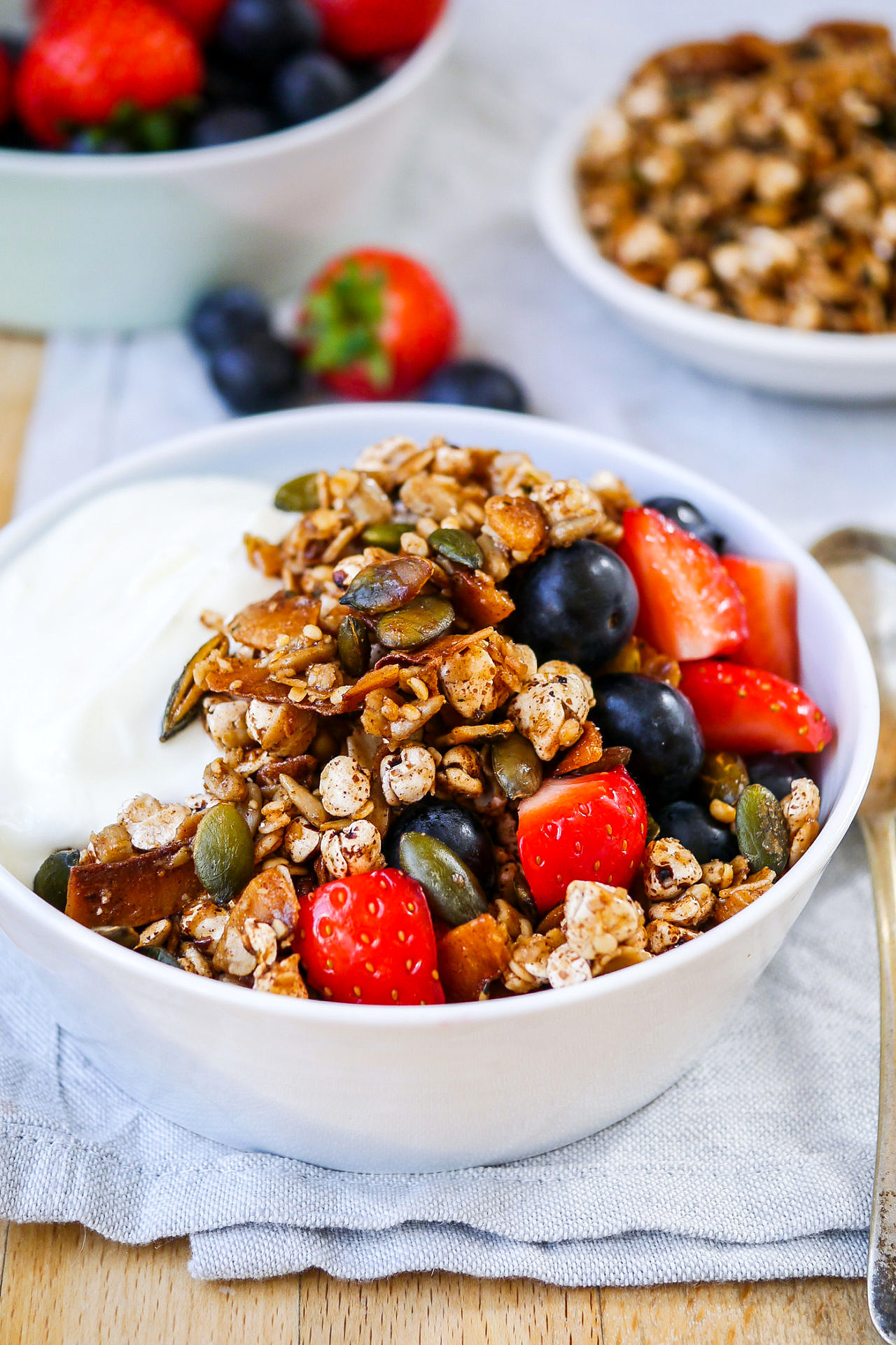 side view of a small blue bowl with Greek yoghurt, toasted muesli and berries on a wooden table