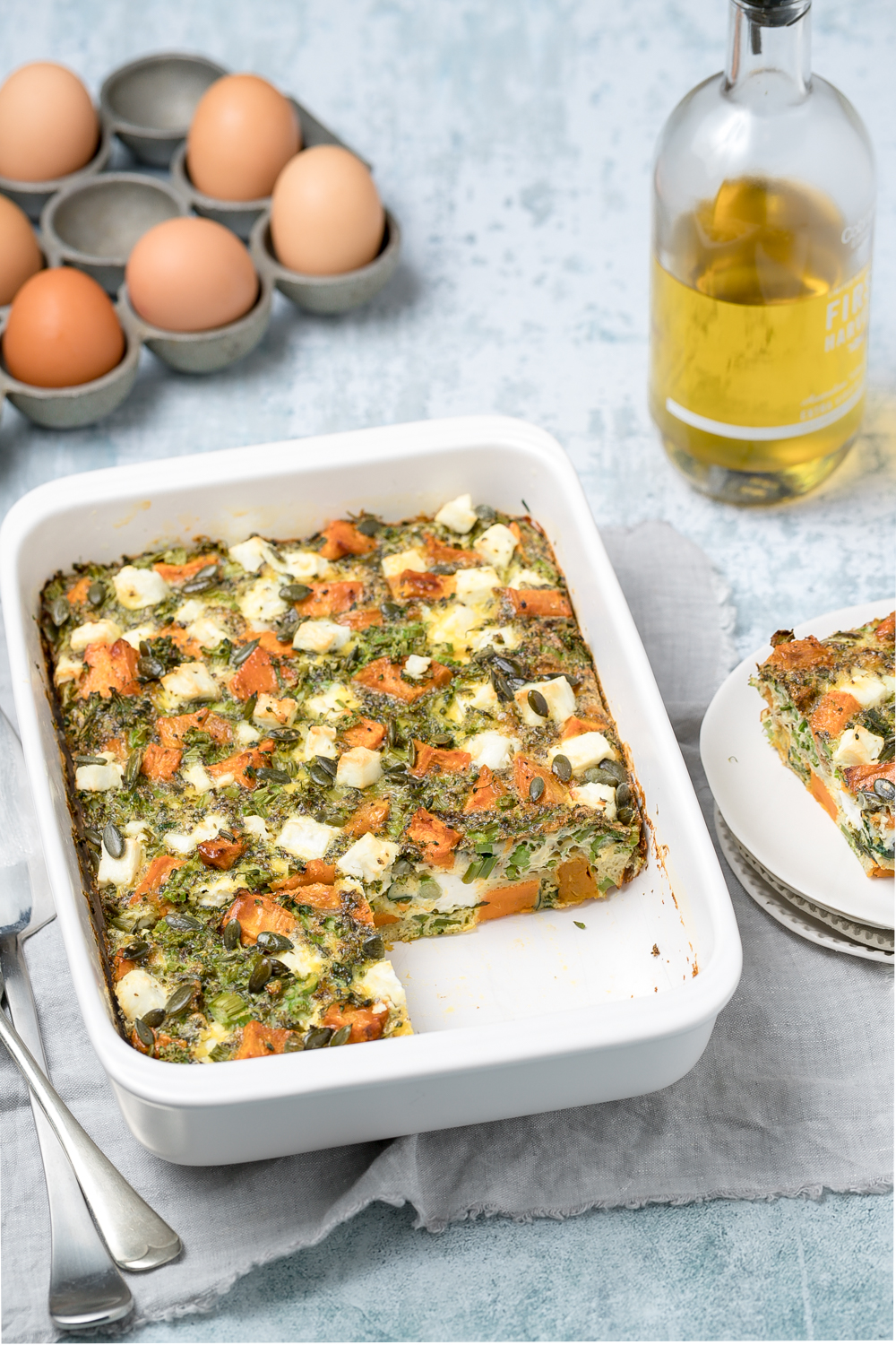 White rectangular baking dish with sweet potato, broccoli and feta frittata. Eggs and olive oil bottle in background