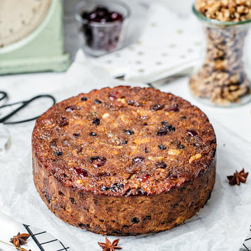 Healthy Christmas fruit cake on top of baking paper and wire rack, ingredients and scales in background