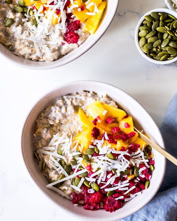 Two ceramic bowls with overnight oats, mango, coconut and raspberries