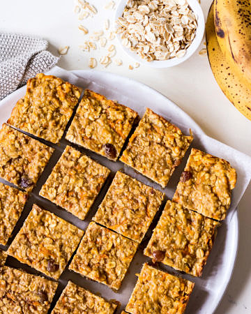 Banana oatmeal bars on a white plate with rolled oats and bananas