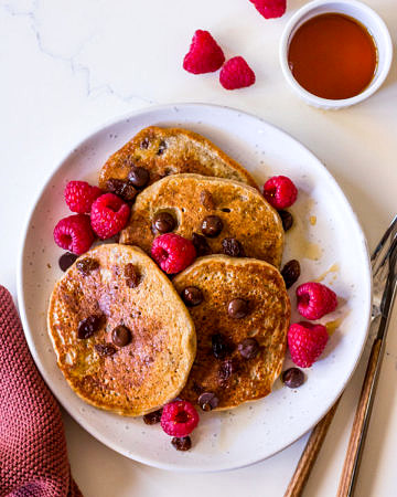 Vegan protein pancakes on white ceramic plate with chocolate chips, raspberries and maple syrup