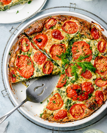 Top down view of a crustless pie made with eggs, ricotta, kale and tomatoes