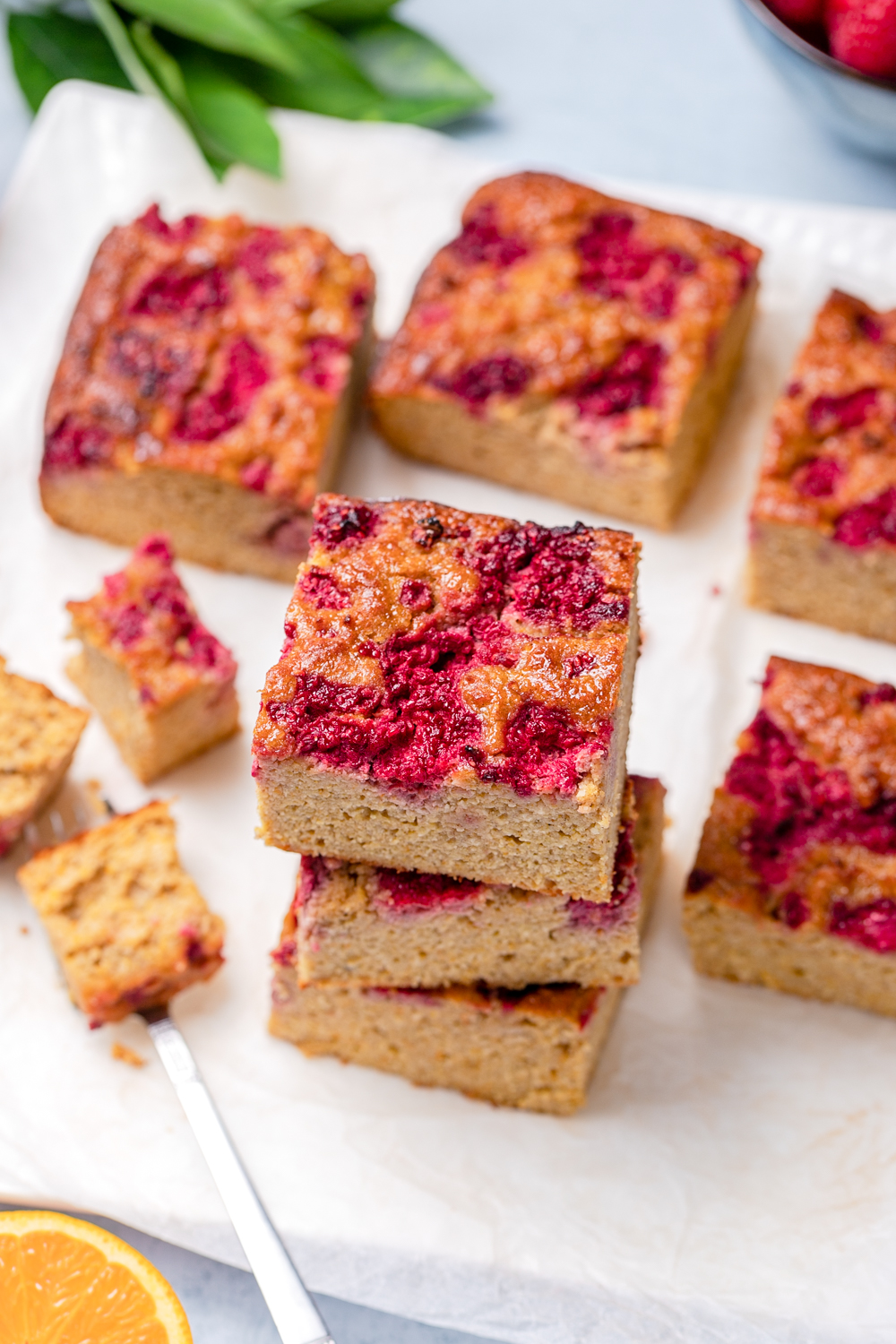 Squares of healthy orange almond cake stacked, topped with raspberries
